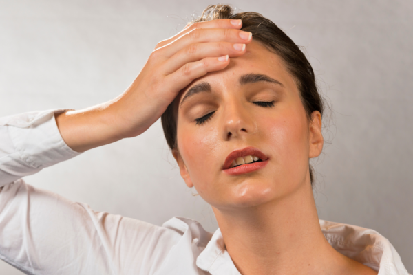woman with hand on forehead and eyes closed